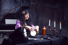 Sorceress in her room. Sorceress working with crystal ball in her room stock photography