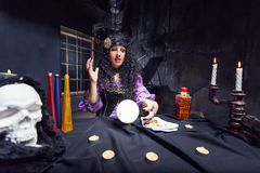 Sorceress in her room. Sorceress working with crystal ball in her room Royalty Free Stock Photography