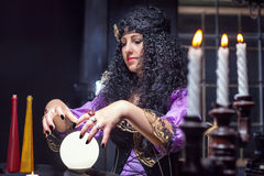 Sorceress in her room. Sorceress working with crystal ball in her room Royalty Free Stock Image