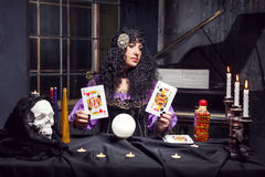 Sorceress while practising witchcraft. Sorceress practising witchcraft with cards in her room Royalty Free Stock Photos