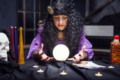 Sorceress while practising witchcraft. Sorceress looking at crystal ball in her room royalty free stock photo