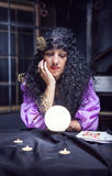 Sorceress while practising witchcraft. Sorceress looking at crystal ball in her room stock image