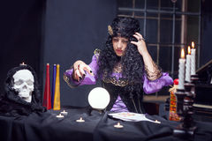 Sorceress while practising witchcraft. Sorceress looking at crystal ball in her room royalty free stock photography