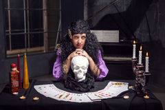 Sorceress while practising witchcraft. Sorceress practises witchcraft with pack of cards leaning on the skull Stock Image