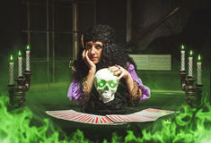 Sorceress practising witchcraft. Sorceress practises witchcraft using the skull, green smoke in the room stock images