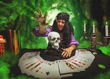 Sorceress while practising witchcraft. Strong sorceress practises witchcraft using pack of cards and the skull stock photos