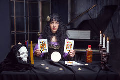 Sorceress while practising witchcraft. Sorceress working with cards and crystal ball in her room Royalty Free Stock Photos