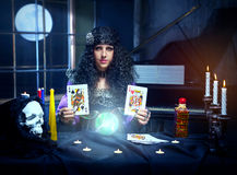 Sorceress while practising witchcraft. Sorceress working with cards and crystal ball in her room, crystal ball is glowing Stock Image