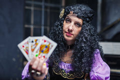 Sorceress while practising witchcraft. Sorceress working with cards and crystal ball in her room, crystal ball is glowing stock images