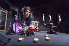 Sorceress while practising witchcraft. Sorceress working with cards in her room, candles on the table Stock Photography