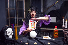 Sorceress while practising witchcraft. Young sorceress working with king card looks in the camera stock photography