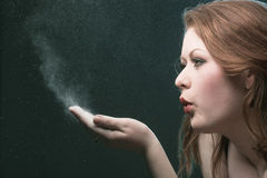 Sorcery. The girl blows off a dust from a palm Royalty Free Stock Image