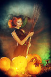 Sorcery. Beautiful red-haired witch casts a spell over pumpkins. Halloween Royalty Free Stock Images