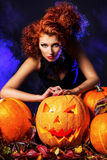 Sorcery person. Beautiful red-haired witch casts a spell over pumpkins. Halloween Royalty Free Stock Photos