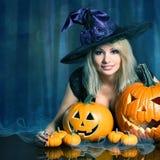 Sorcière avec des potirons de Halloween photographie stock