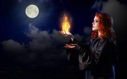 Sorcière avec la flamme sur le fond de ciel nocturne Images stock