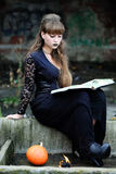 Sorcière avec un livre des charmes Photo stock