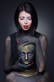 Sorcière de deux filles en peinture noire avec des ornements d'or photos stock