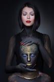 Sorcière de deux filles en peinture noire avec des ornements d'or image stock