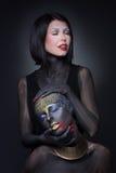 Sorcière de deux filles en peinture noire avec des ornements d'or images libres de droits