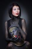 Sorcière de deux filles en peinture noire avec des ornements d'or photographie stock