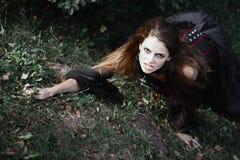 Sorcière de Halloween dans une belle jeune femme de forêt foncée dans le costume de sorcières Conception d'art de Halloween Fond  Images libres de droits