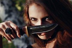 Sorcière de Halloween dans une belle jeune femme de forêt foncée dans le costume de sorcières Conception d'art de Halloween Fond  Image stock