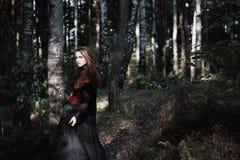 Sorcière de Halloween dans une belle jeune femme de forêt foncée dans le costume de sorcières Conception d'art de Halloween Fond  Photos libres de droits