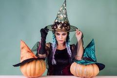 Sorcière de Veille de la toussaint dans le chapeau noir sur le balai Femme posant avec le potiron Lanterne principale de cric de  photos libres de droits