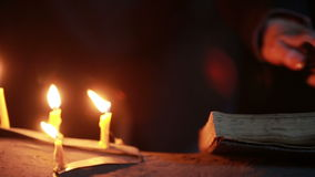 Sorcière tenant le rituel magique Vieux livre et bougie Veille de la toussaint banque de vidéos