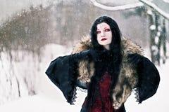 Sorcière de noir de Cosplay dans la forêt d'hiver Photo libre de droits