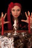 Sorcière à la table avec des bougies.   Image stock
