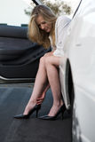 Sore ankle. Pretty blond woman in white blouse and black skirt sitting in a white car with legs out putting on sexy black high heel shoes rubbing sore ankle Royalty Free Stock Images