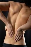 Sore back. Back view of young man touching aching back Stock Photography