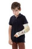 Sore broken arm. Young boy looking unhappy with a broken arm stock images