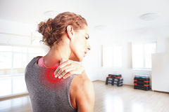 Sore after hard workout at fitness. Portrait of sporty woman puting her hand on red spot on while has sport injury in her shoulder Royalty Free Stock Photo