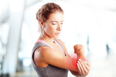 Sore after hard workout at fitness. Portrait of sporty woman puting her hand on red spots on while has sport injury in her elbow Royalty Free Stock Photo