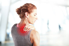Sore after hard workout at fitness. Portrait of sporty woman puting her hand on red spots on while has sport injury in her shoulder Stock Photo