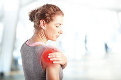 Sore after hard workout at fitness. Portrait of sporty woman puting her hand on red spots on while has sport injury in her shoulder Royalty Free Stock Image