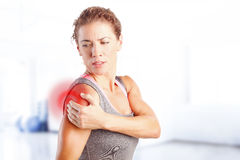 Sore after hard workout at fitness. Portrait of sporty woman puting her hand on red spots on while has sport injury in her shoulder Stock Photos