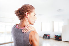 Sore after hard workout at fitness. Portrait of sporty woman puting her hand on shoulder while has sport injury Royalty Free Stock Image