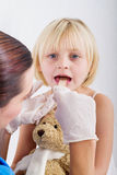 Sore throat. A little girl having her sore throat checked by a doctor in hospital Stock Photography