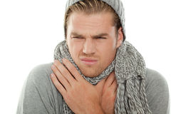 Sore throat. Blond man with scarf and cap Royalty Free Stock Photography