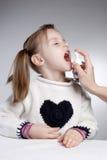 Sore throat. Little girl taking sore throat medication Stock Photography