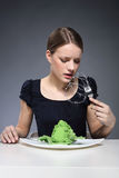 Sore throat, difficulty in swallowing. Young girl sitting over a plate of vegetables and put into the mouth barbed wire stock images