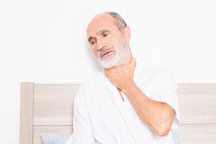 Sore throat. Elderly man sitting on bed suffering from throat problems royalty free stock photos