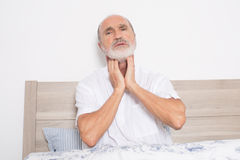 Sore throat. Elderly man sitting on bed suffering from throat problems stock image