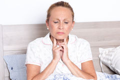 Sore throat. Elderly woman in bed with sore throat royalty free stock photography