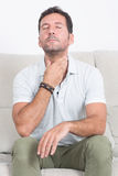 Sore throat on gray background. Man in white polo shirt sitting on sofa and needs medication royalty free stock photo