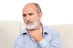 Sore throat man. Elderly man sitting suffering from throat problems royalty free stock photography